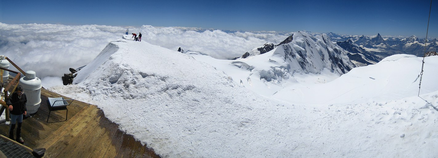 Zumsteinspitze and Signalkuppe: on top of Signalkuppe; on the left side: snow melting machine of Rifugio Regina Margherita; from center to right in the background: Lyskamm,  Breithorn, Matterhorn, Dent Blanche