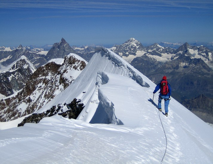 Lyskamm ridge traverse and Castor: Rainer on the ridge traverse from Lyskamm East to Lyskamm West summit with big cornice; in the background from left to right: Dent d'Herens, Matterhorn, Dent Blanche, Grand Cornier, and Obergabelhorn