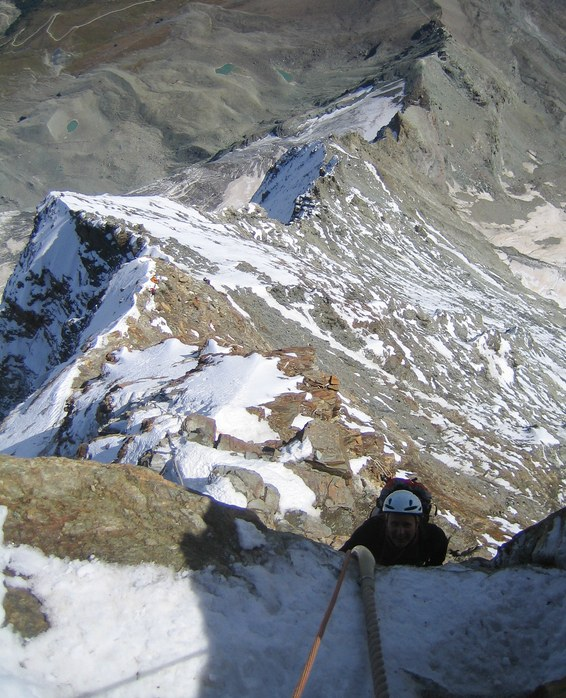 Matterhorn via Hörnli ridge: Peter climbing up the Moseley slabs with Hörnli ridge and Hörnli hut in the background