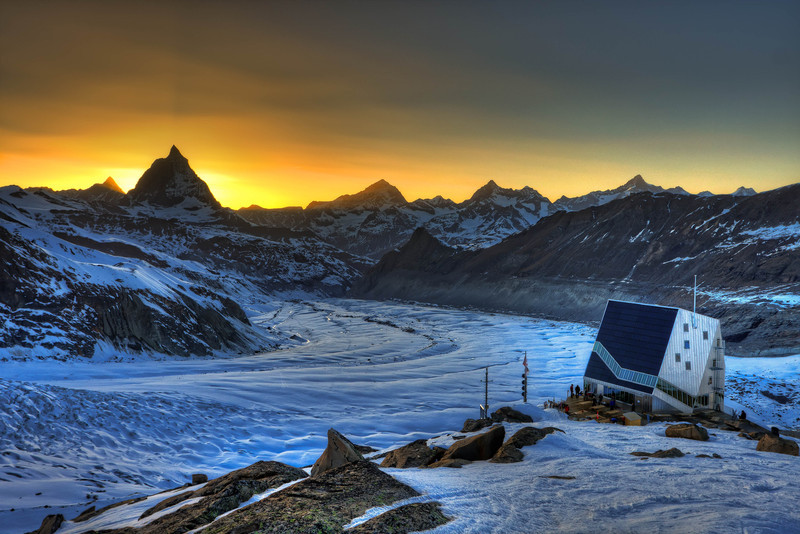 The new Monte Rosa hut with Matterhorn, Dent Blanche and a few more 4000 m peaks at sunset (HDR photo) (keywords: alpen, alps, berg, berge, berghütte, dent blanche, gornergrat, hdr, leute, matterhorn, monte rosa hut, obergabelhorn, person, schweiz, sonnenuntergang, switzerland, valais, wallis, wellenkuppe, wolke, wolken, zinalrothorn, clouds, glacier, mountain, mountain hut, mountains, people, sunset, swiss)